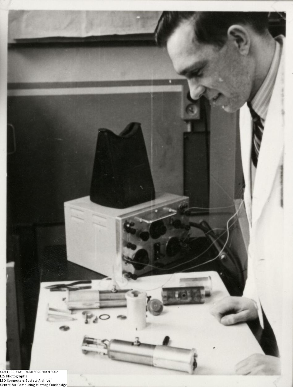 Photograph of 61301  Ray Shaw with mercury delay line parts (June 1950)